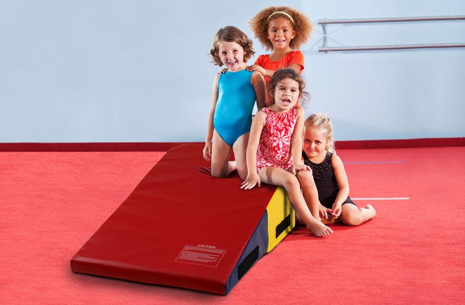 Beginner gymnasts with a wedge mat in a gymnastics studio